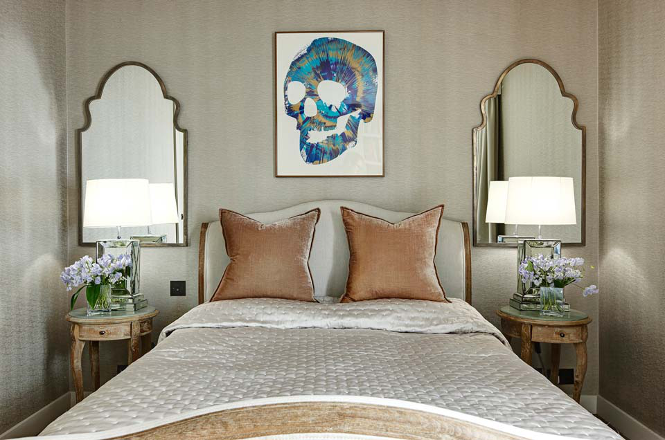 The daughter's bedroom has an antique French bed and night stands. The wall covering is from Harlequin and the bedside lamps and mirrors are from Michael Reeves. The artwork was done by the daughter herself.