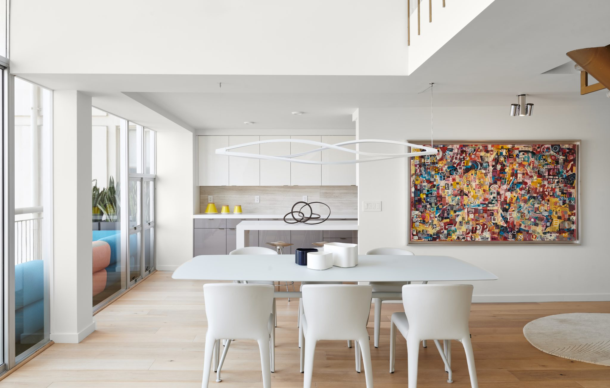 Several of the home's furnishings reference the 1960s', when the house was originally built. The supended light fixture from Nemo Lighting breaks up the space between the ceiling andwhitetable with curved corners, fromRimadesio. The Hola Cassina chairs weredesigned by Hannes Wettstein. Bringing a burst of color to the space,the vibrant painting was created by Dutch artist Micha Tauber.