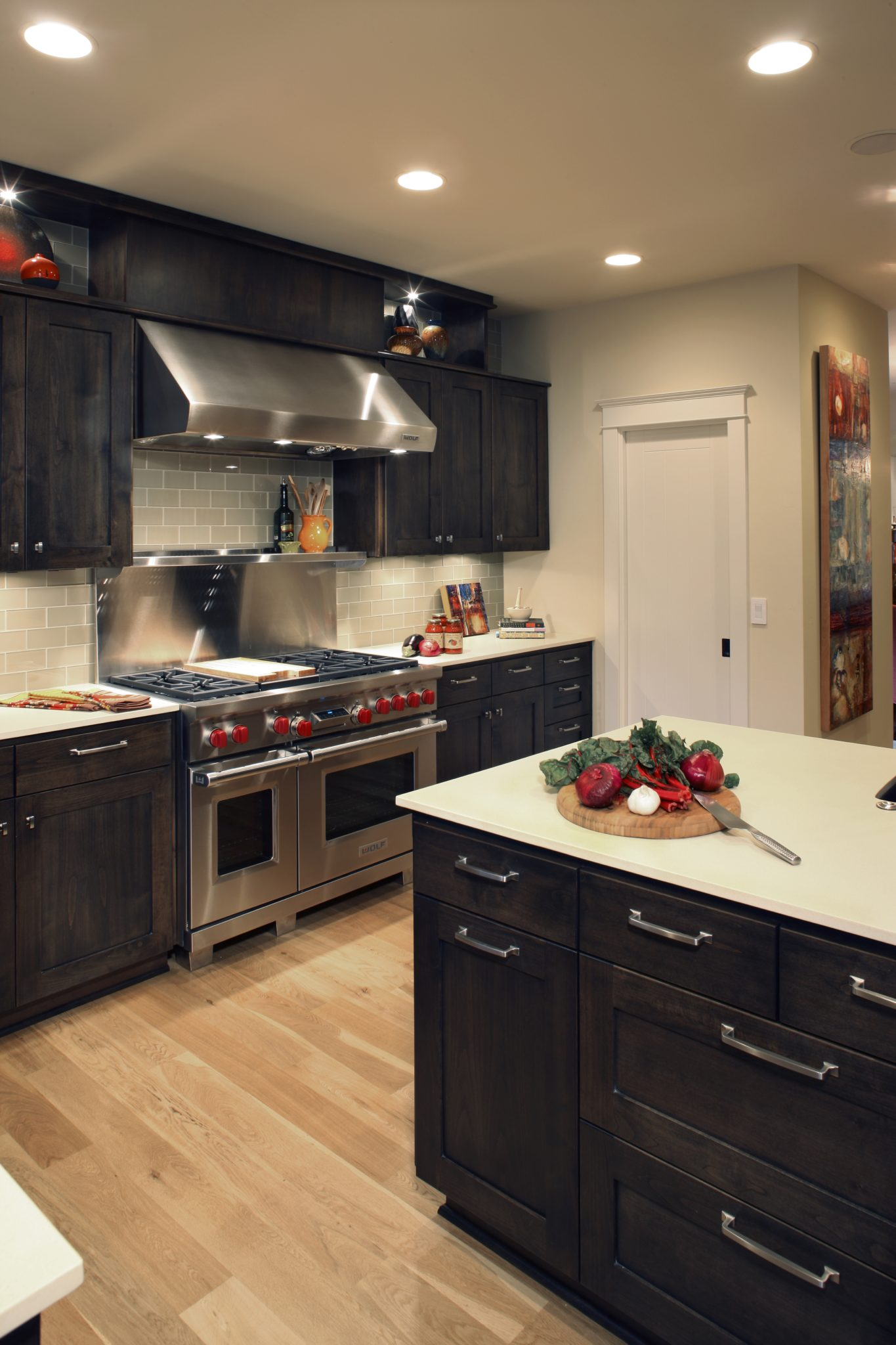 Neoclassical kitchen with subway tile backsplash and dark wood cabinets by PepperJack Interiors