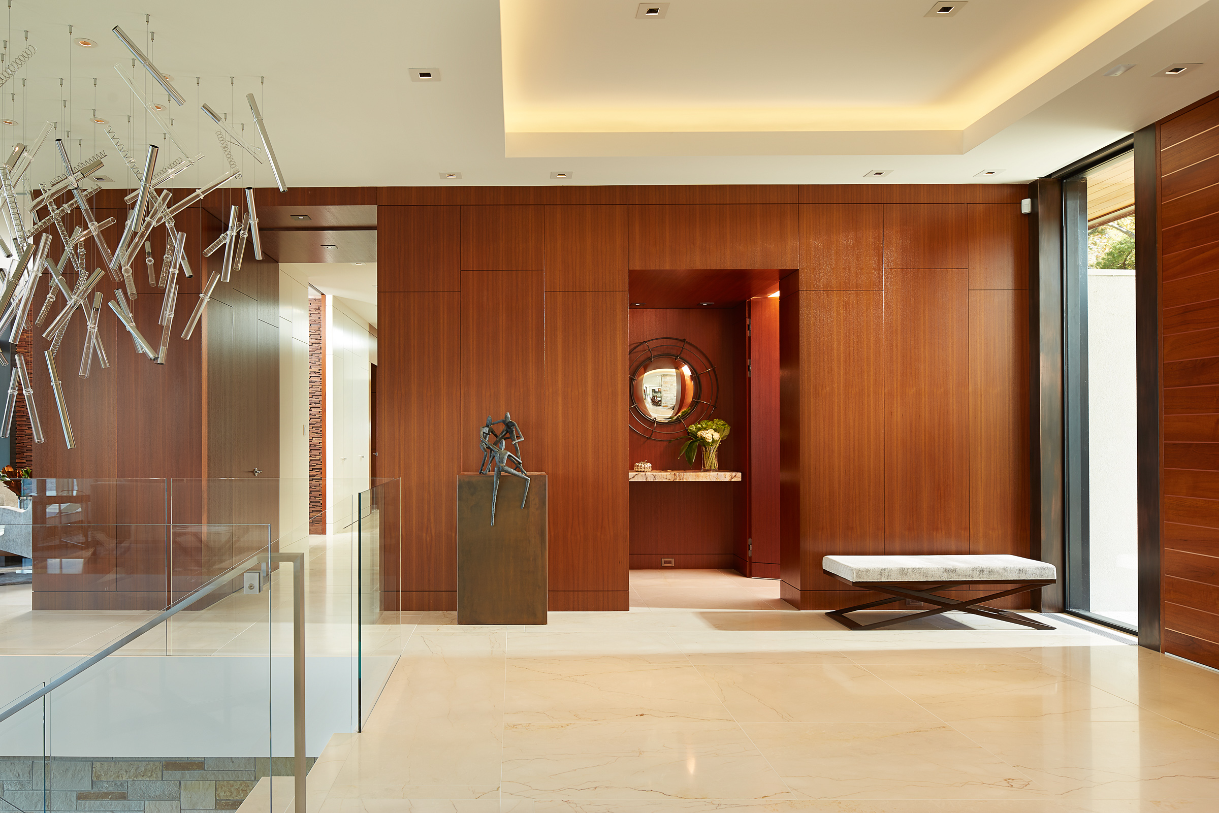 Custom teak designed wall panels conceal doors, closets and storage cabinets. by Alene Workman Interior Design