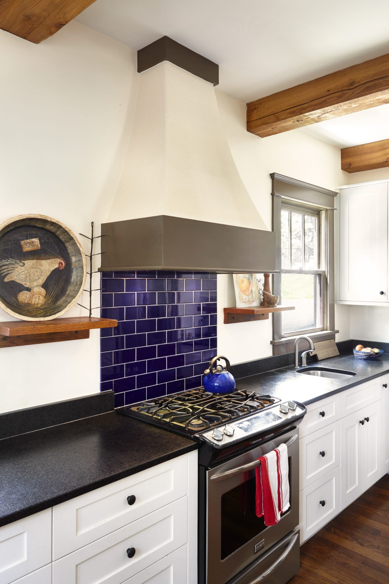 Cobalt blue tile mixes with rustic exposed beams in this craftsman kitchen by Marcelle Guilbeau Interior Design