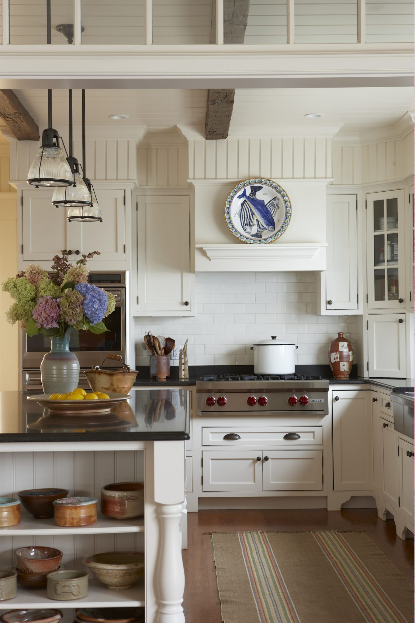 A timeless kitchen gives a country feel by adding pottery and a striped textured rug. By Gil Walsh Interiors