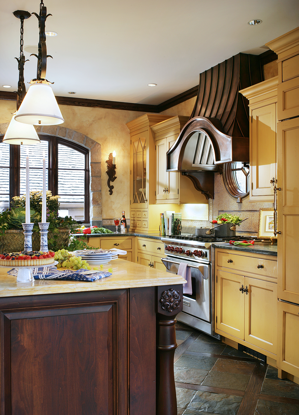 French Country kitchen with timeless old world ambiance, featuring mustard-colored cabinets, wrought iron light fixtures, limestone and soapstone counters, and a slate and wood floor. By J. Stephens Interiors