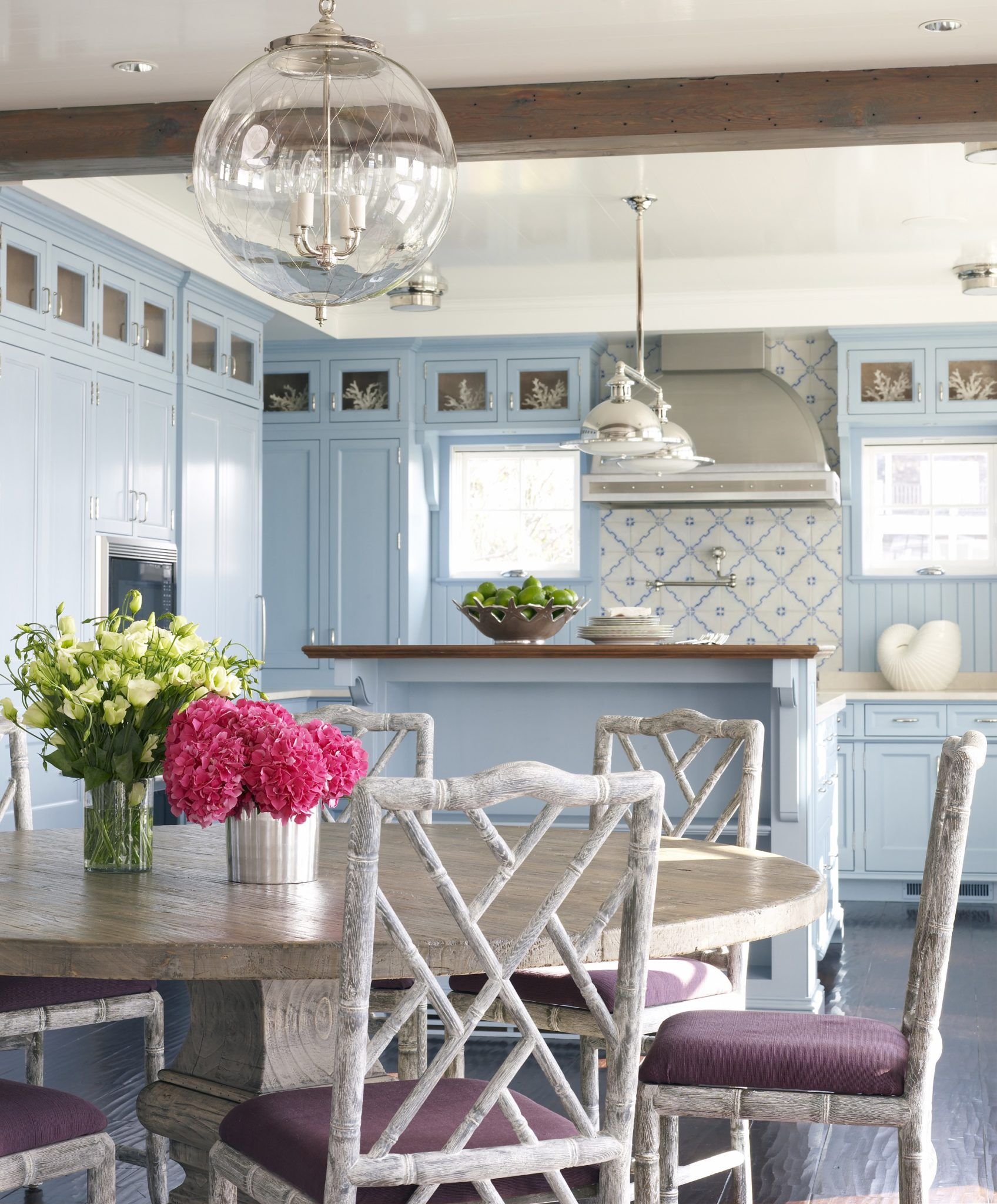 This light, airy kitchen features traditional blue cabinetry. by Sarah Blank Design Studio