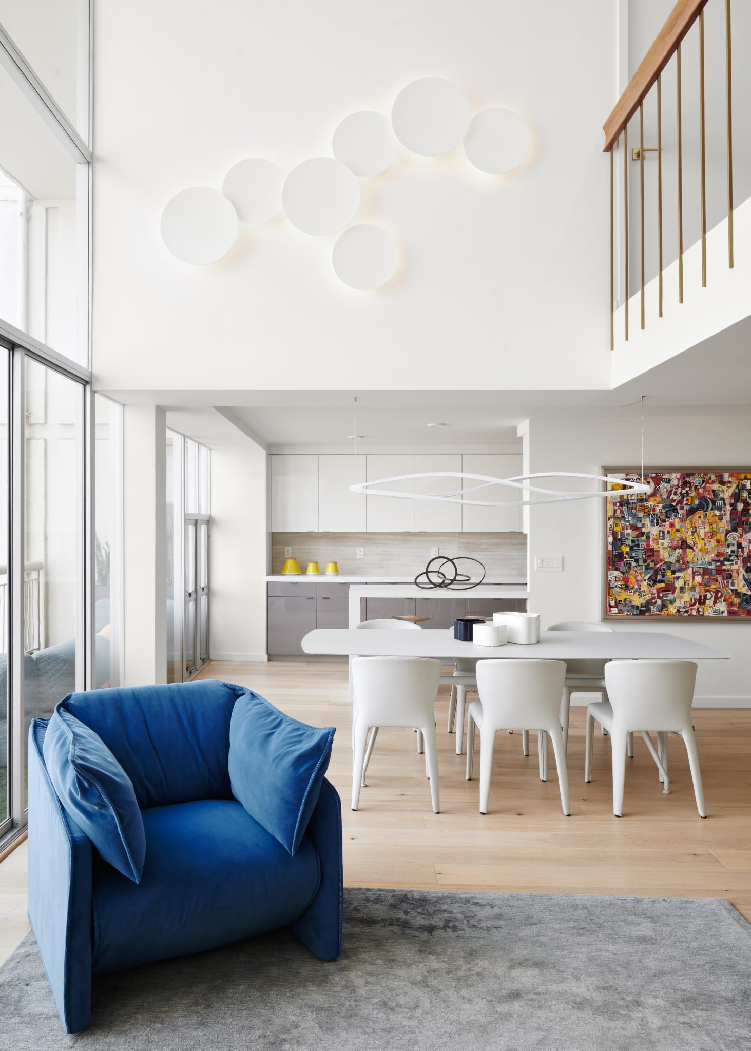 Here, a unique armchairfrom Poltrona Frau, upholstered in blue velvet,delivers subdued color. The sculptural sconce near the open landing is from Vibia, and the rug was custom-designed by Isolina Mallon Interiors and crafted by Scott Studio Group.