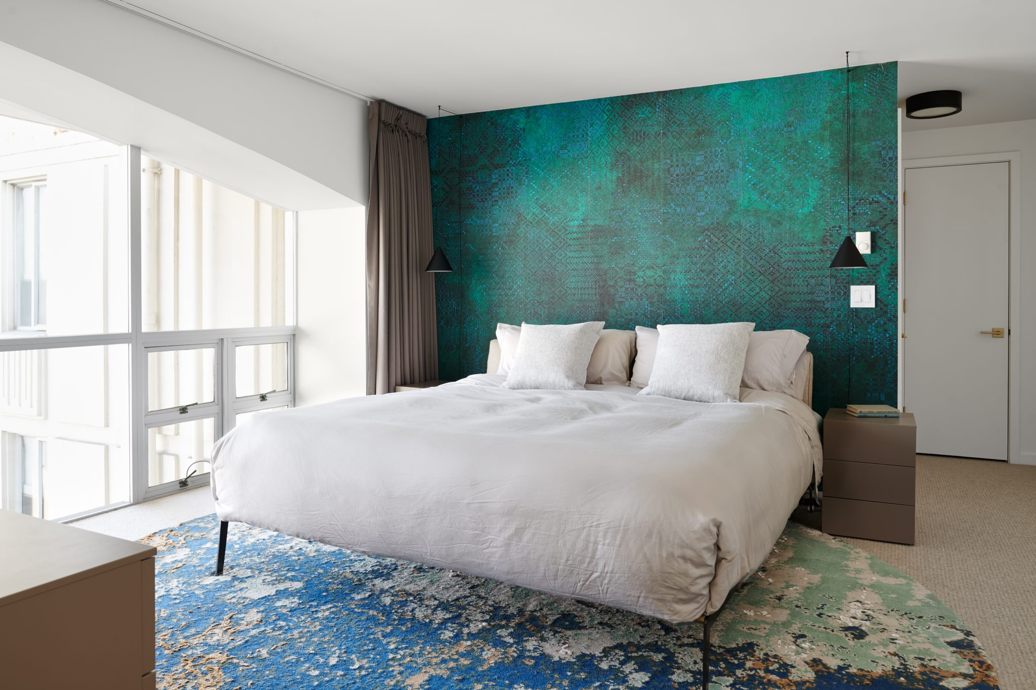 A peacock-coloredaccent wall, crafted by Wall&decò, juxtaposes with the steel frame of the Flexform bed designed by Citterio, as the wall'sshades of blue and green also integrate with the colors of the custom rug. Black-out drapery from Création Baumannshields the space from morning light when necessary. The night stands are from Jesse, and the string lights are from Flos.