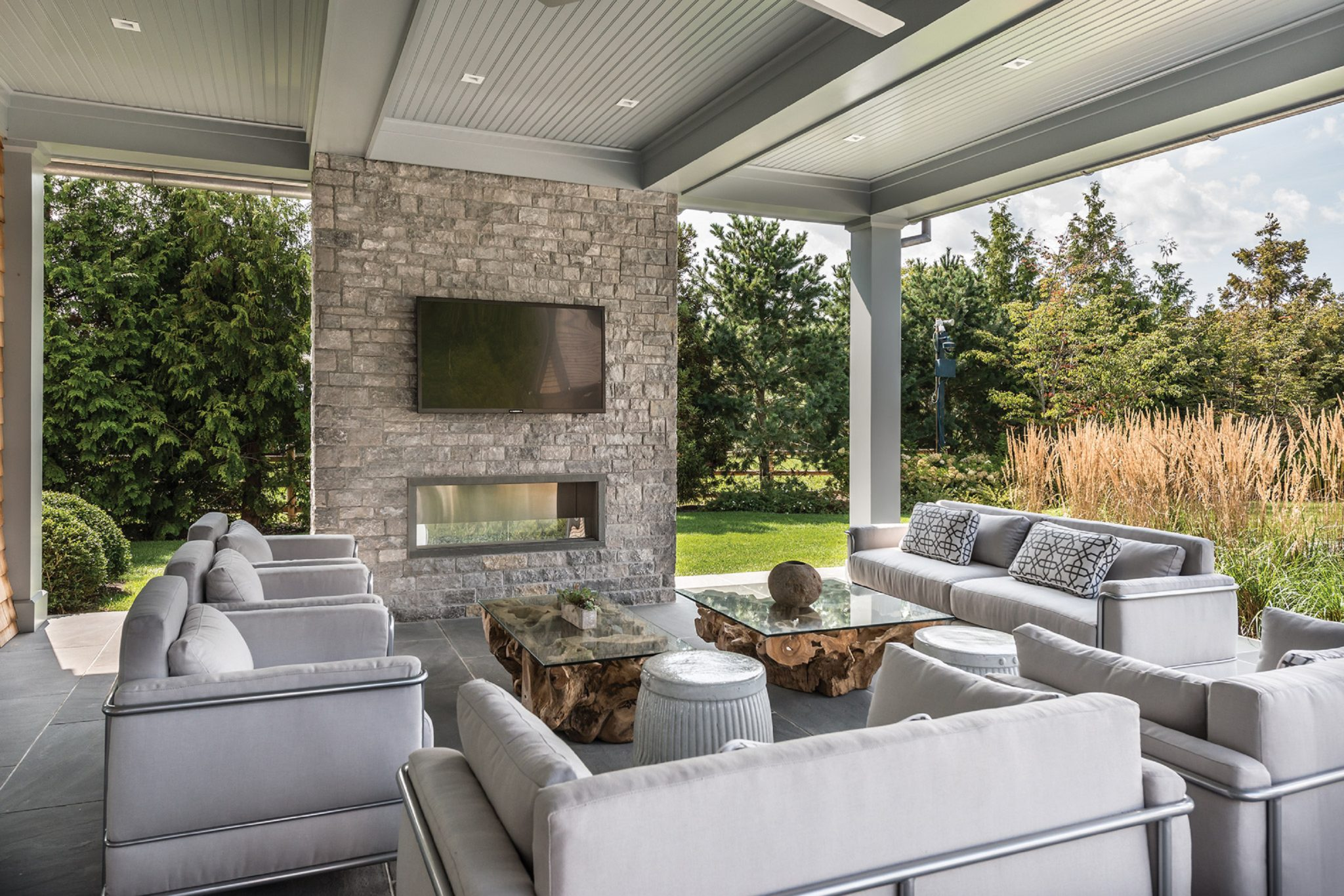 Outdoor Living Room with fireplace and TV by English Country Home