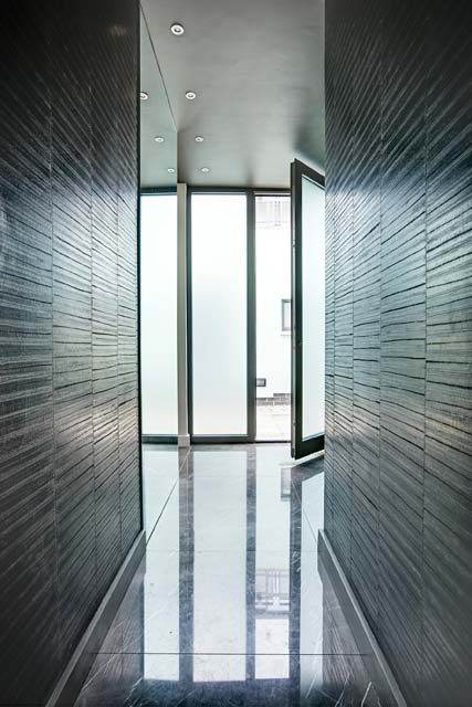 In this hallway, the eel skin wall covering from Elitis at Abbott and Boyd is complemented by a Pietra Grigio marble slab floor.