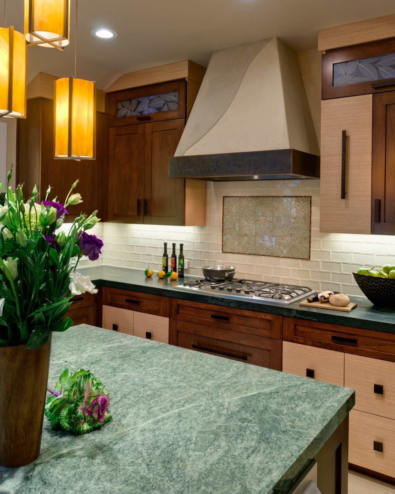 Kitchen showcases green marble, hammered metal hood and glass subway tile by Alison Whittaker Design