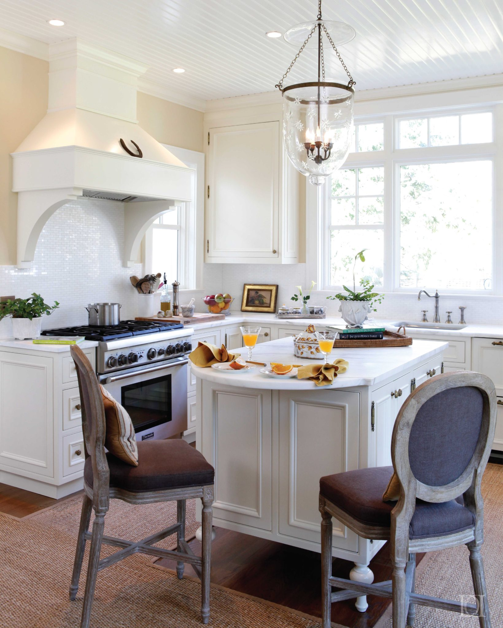 Cottage kitchen with white cabinets, marble counters and island seating by Deborah Leamann Interior Design