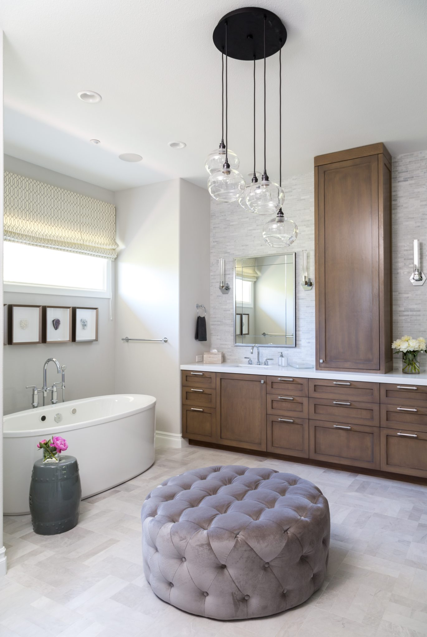 Bathroom featuring custom cabinetry, freestanding tub and chandelier by dmar Interiors
