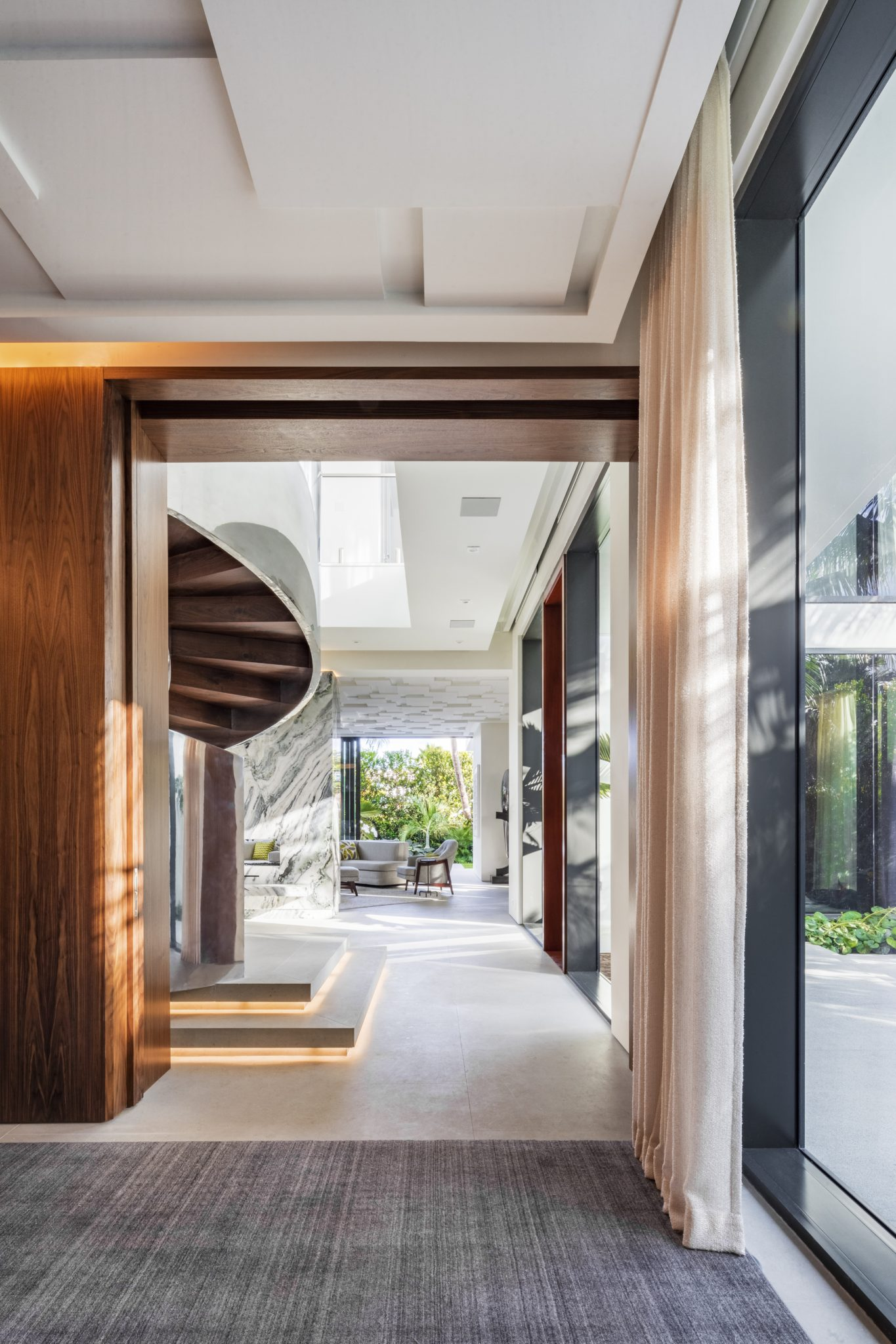 Enfilade of Foyer with highly polished stainless steel and wood spiral staircase by Brown Davis Architecture & Interiors