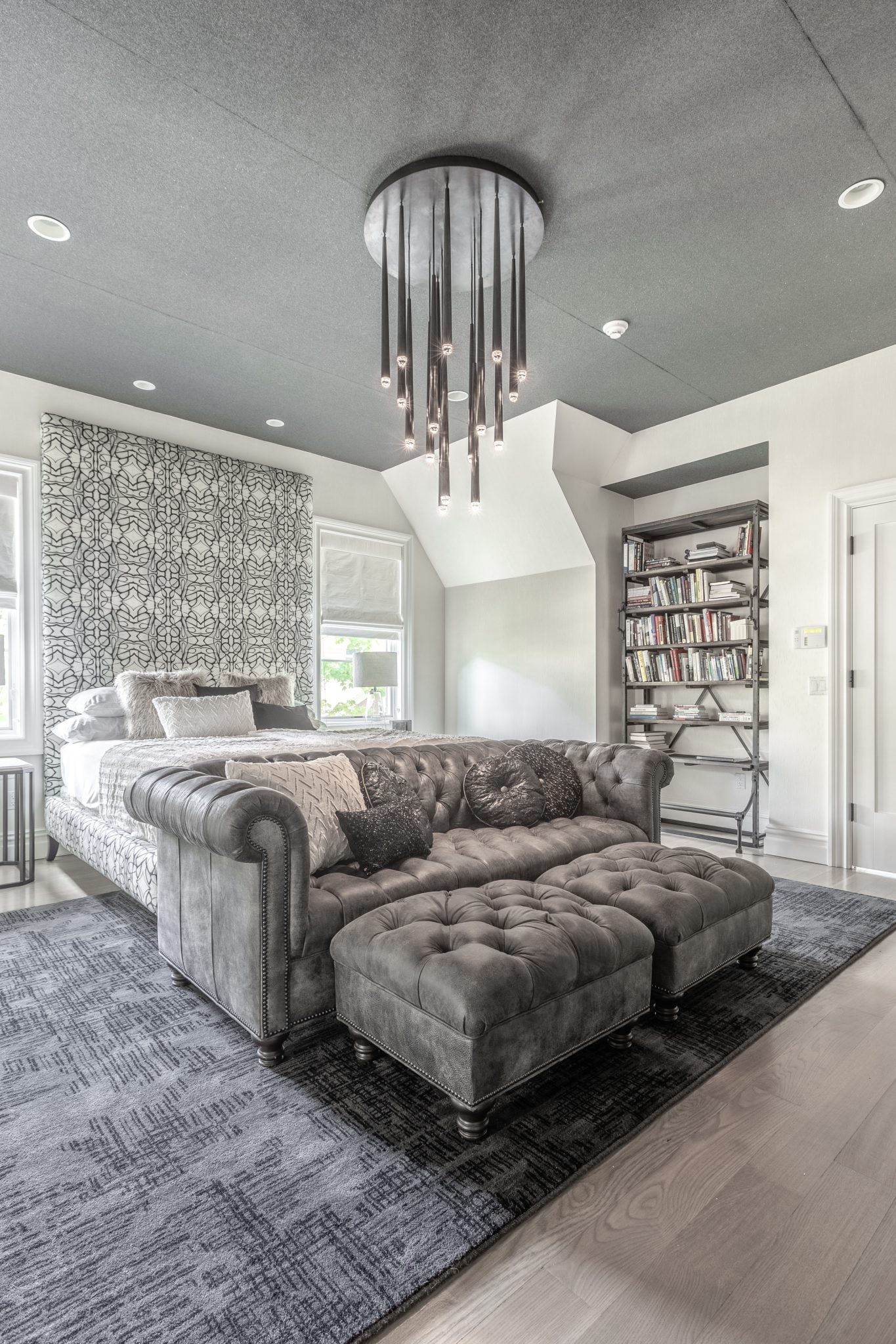 A plush tufted gray couch reposes at the end of the bed with graphic headboard. by Shelley Cekirge Interiors