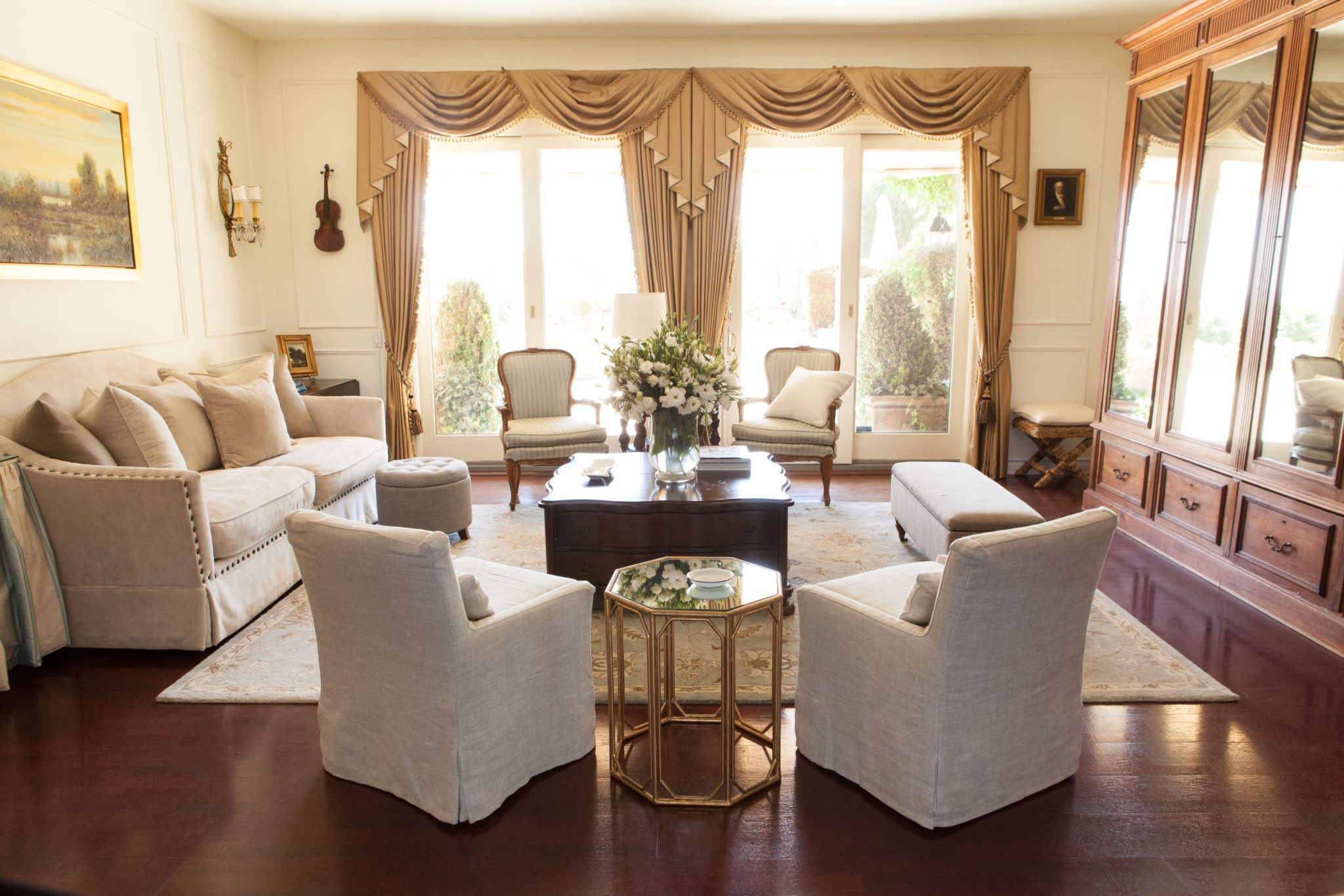 Gold silk drapes and French blue striped antique chairs in a living room by Amodei