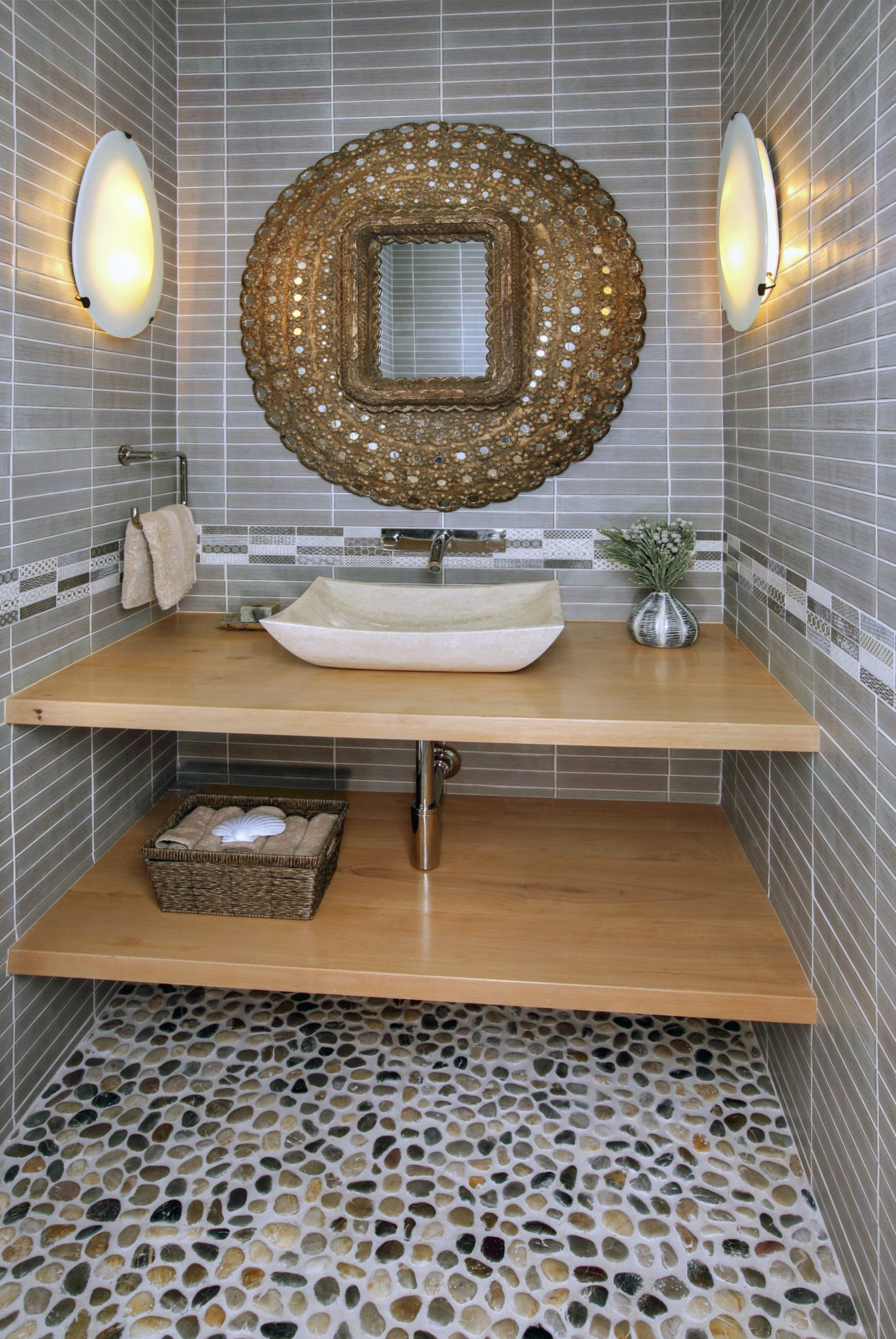 Large multi-toned pebbles set the tone for this powder bathroom. by Sarah Barnard Design