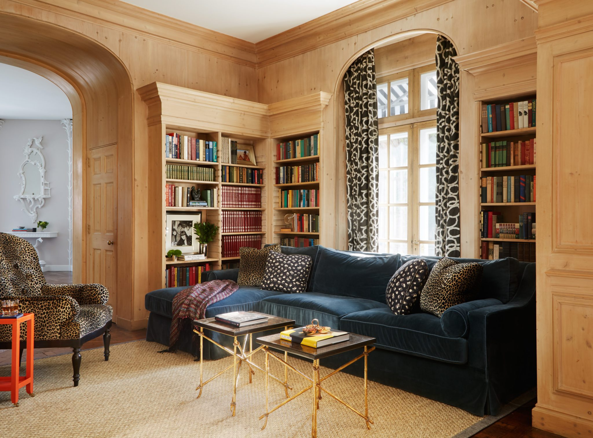 Seating area in library with colorful sofa, patterned drapes and high-back chair by Caitlin Moran Interiors