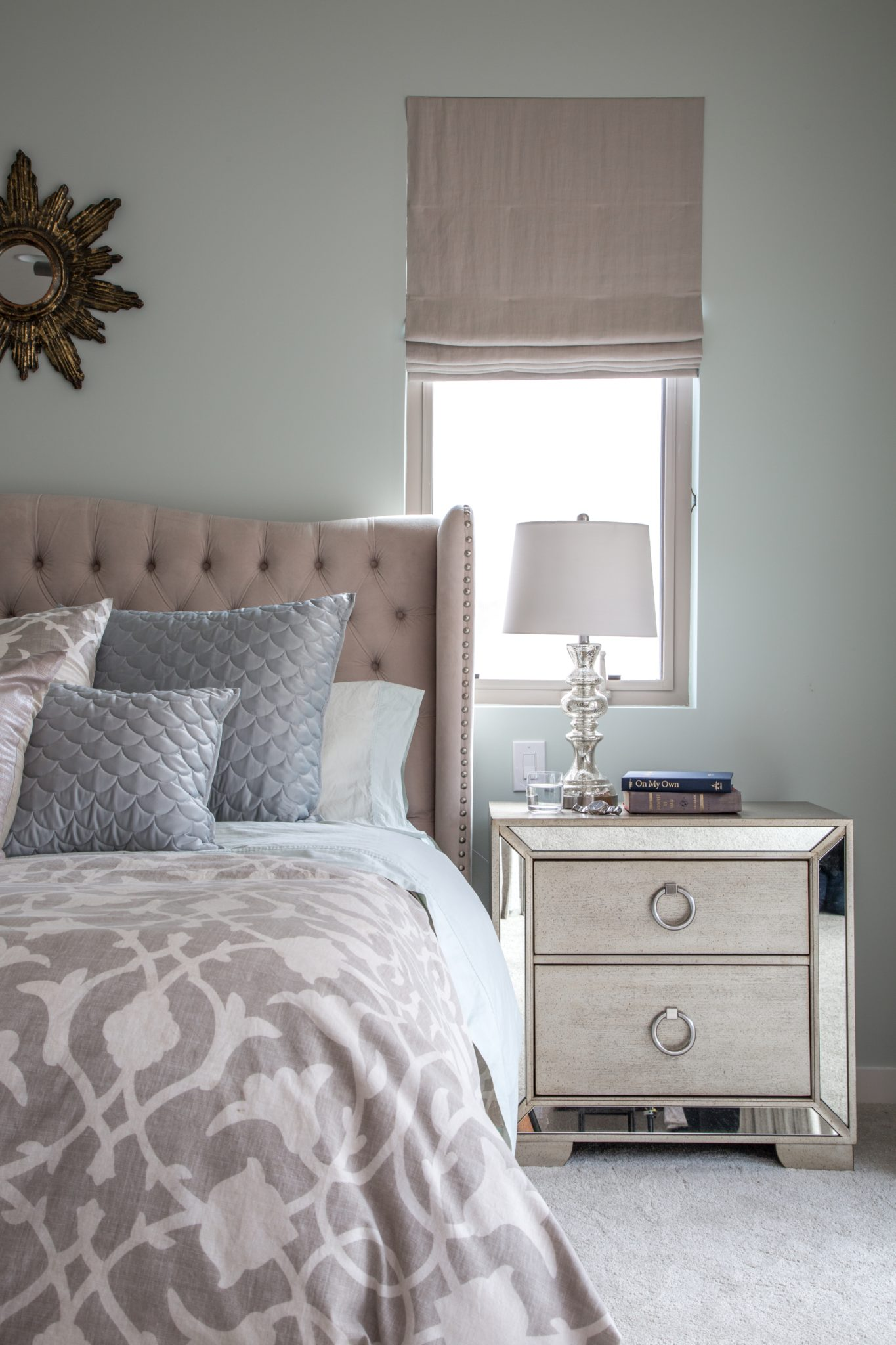 Moody Bedroom withLinen Roman Shadeand Tufted Bed. By dmar Interiors