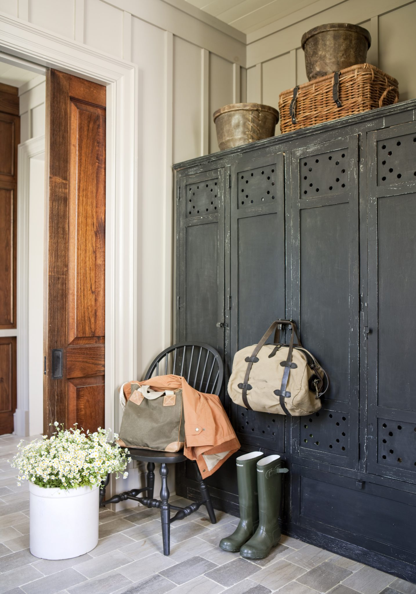 Organic mudroom with paneled walls by Suzanne Kasler Interiors