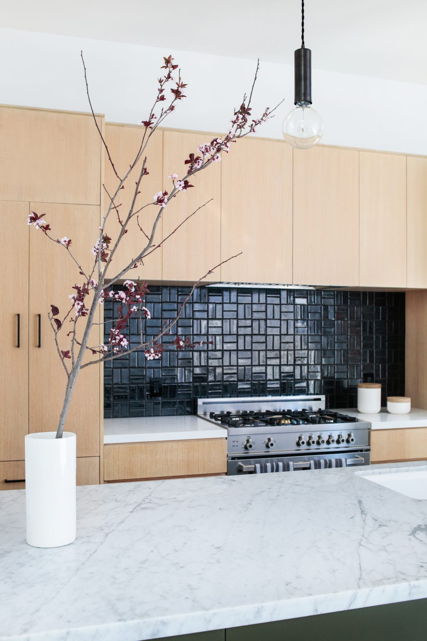 Minimalist gourmet kitchen with oak and marble by Stefani Stein Inc.