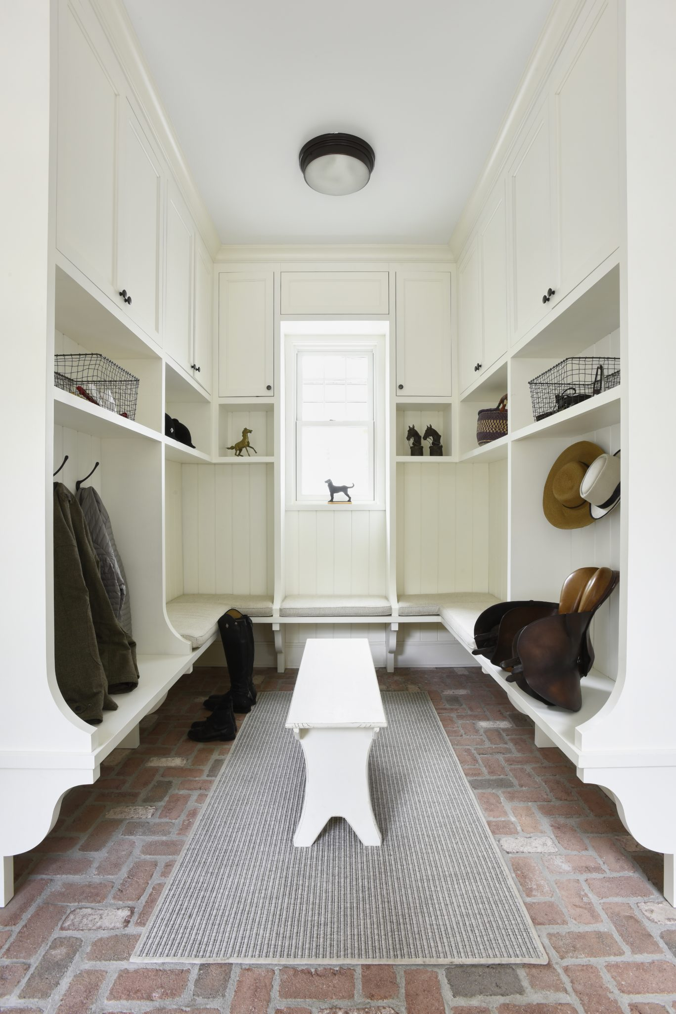 Mudroom with built in bench and cabinets, and brick floor by Huestis Tucker Architects, LLC