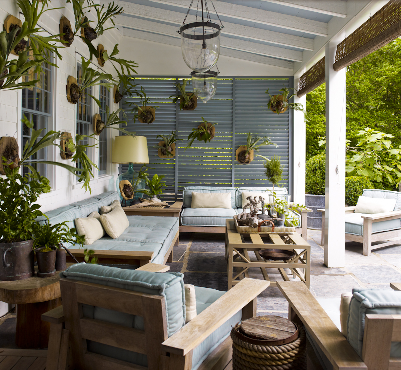 """""""The outdoor living room is the heart of the house and is used well into late fall. The staghorn ferns are used to create my version of a trophy room."""""""