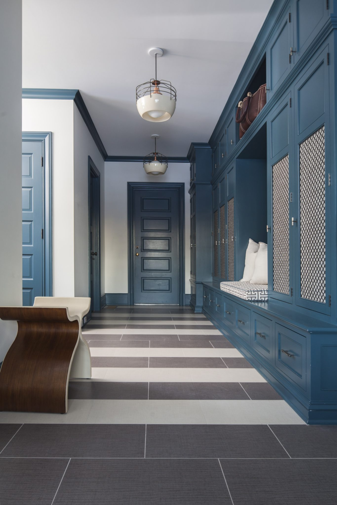 Dark Teal and White Mudroom with Striped Floor by S.B. Long Interiors
