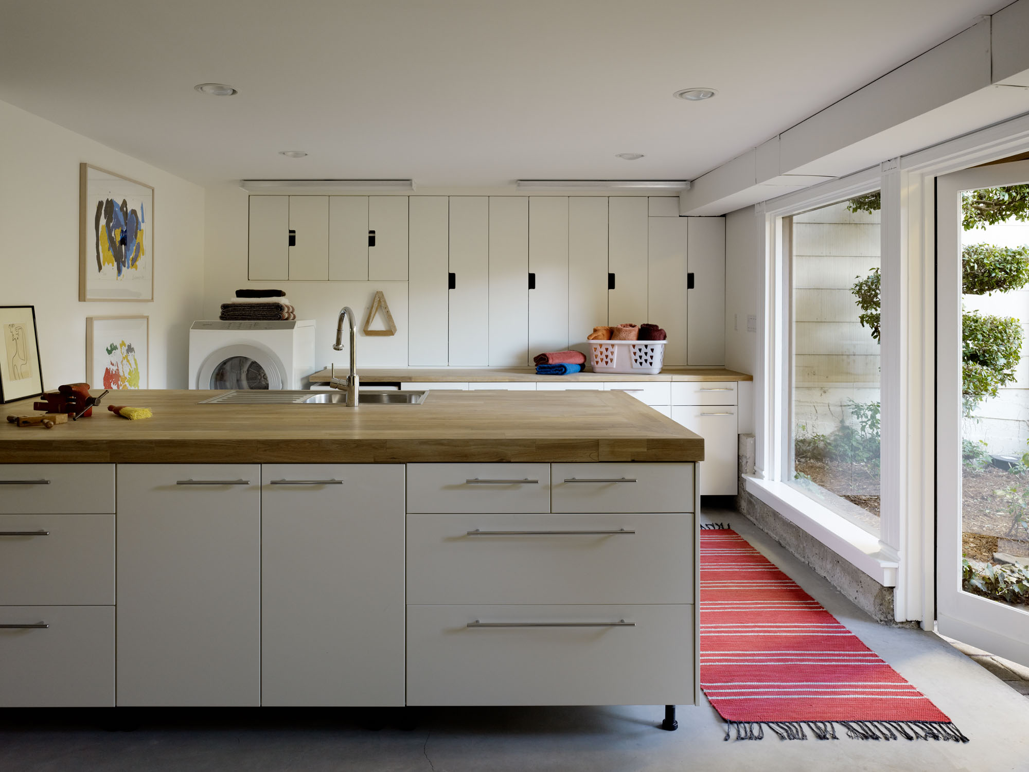Sleek laundry room with wooden counter top by Martin Young Design