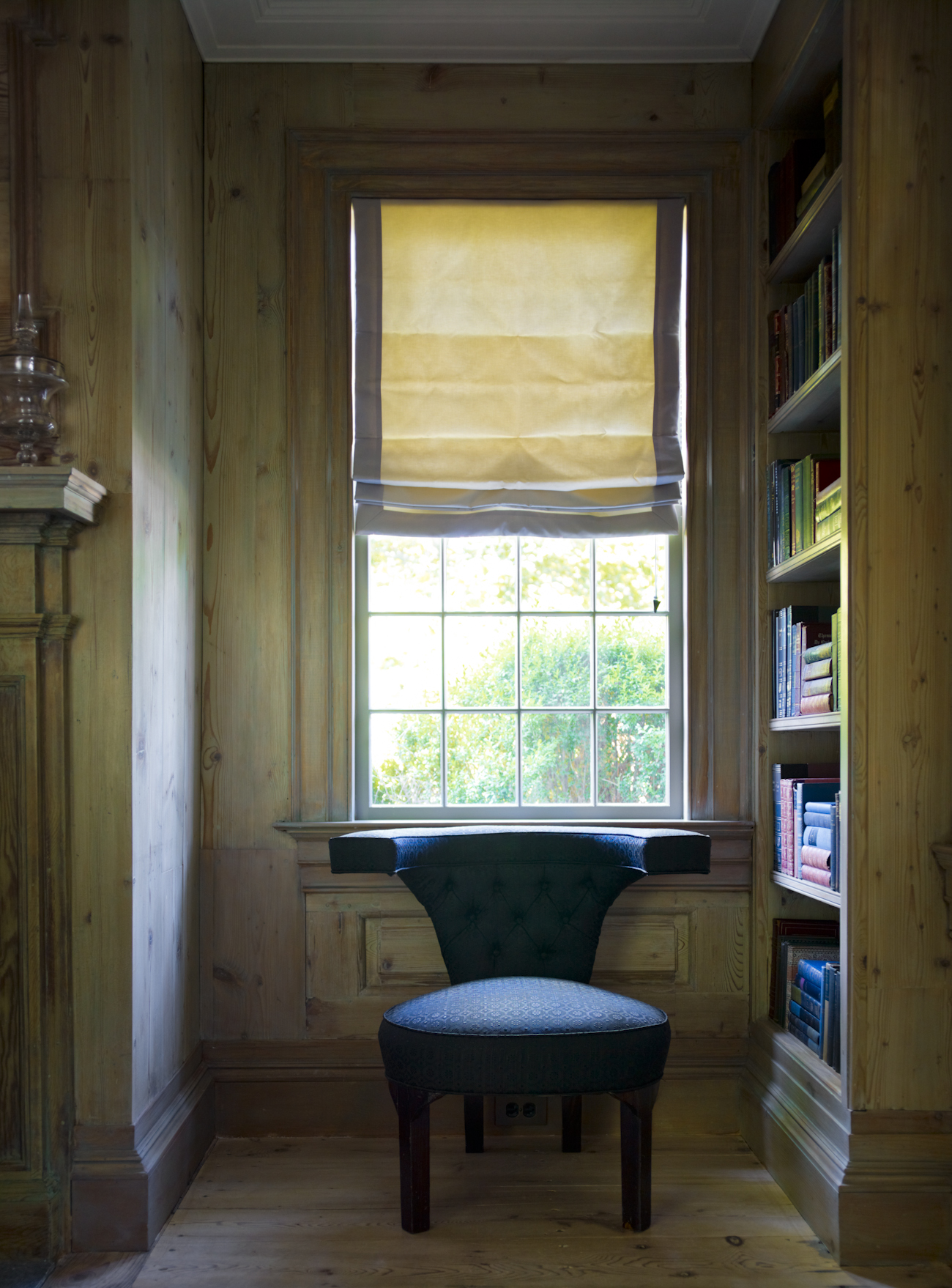 """""""The chair in the library window has the perfect view of all comings and goings. The pine library is made up of a 19th-century paneled room we found at a salvage yard. I designed the carpet, inspired by Italian marbleized bookbinding paper."""""""