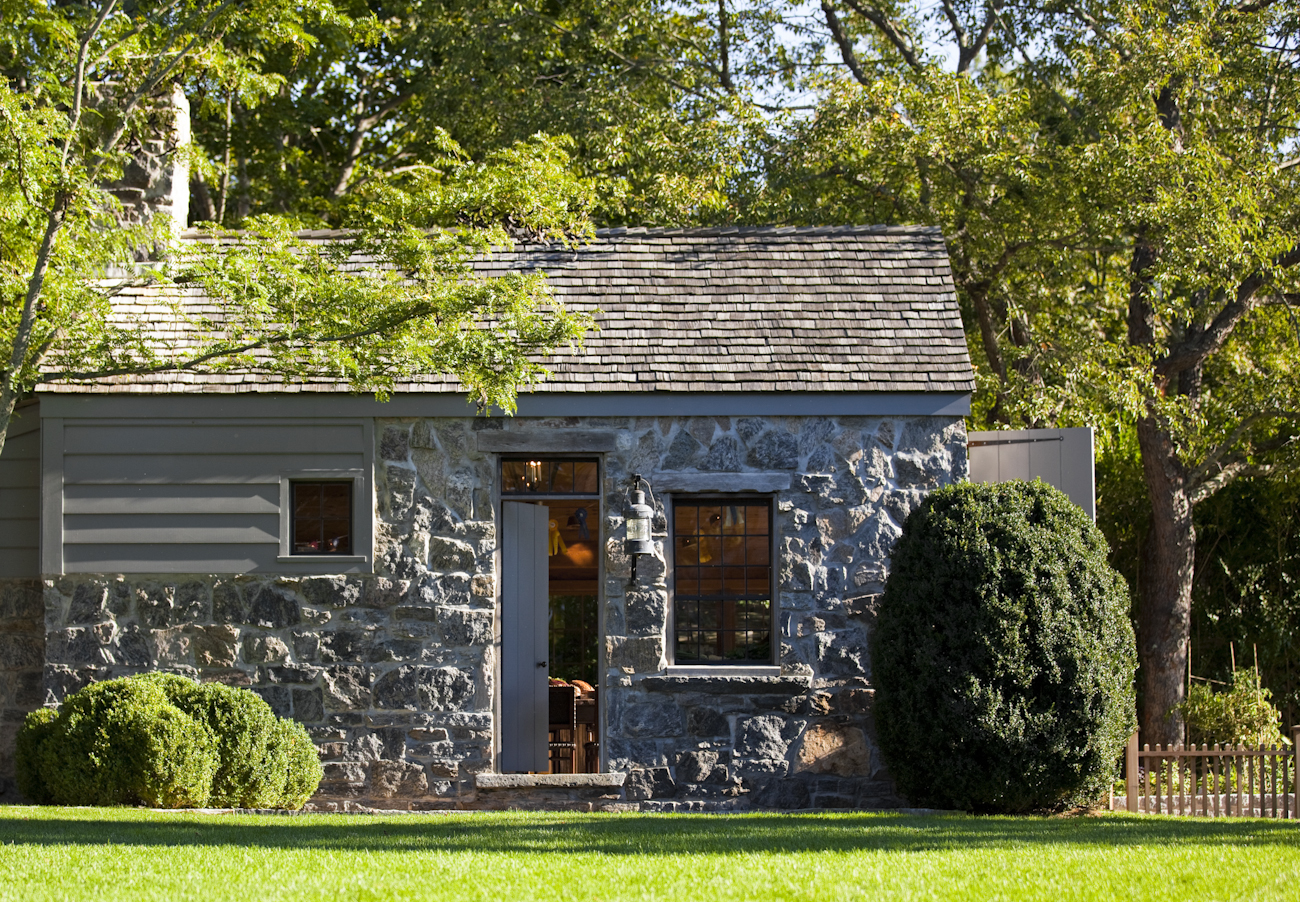"""""""The stone barn was designed loosely on 18th century agrarian structures and boathouses made of stone. The combination of stonework and shiplap blend in with the stone terraces and wooden structures of the property."""""""