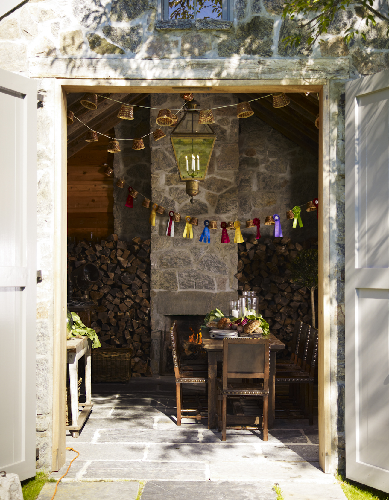 """""""The stone barn is used for dinner parties on cool evenings throughout most of the year. The ceiling beams are the reclaimed floor joists from the main house, replaced during our major renovations of the early 19th century structure."""""""