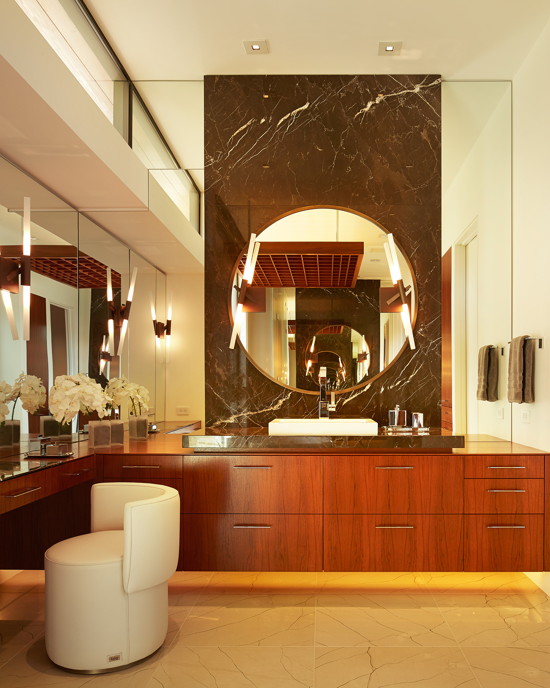 A luminous circular mirror contrasts with dark stone and stained teak. by Alene Workman Interior Design
