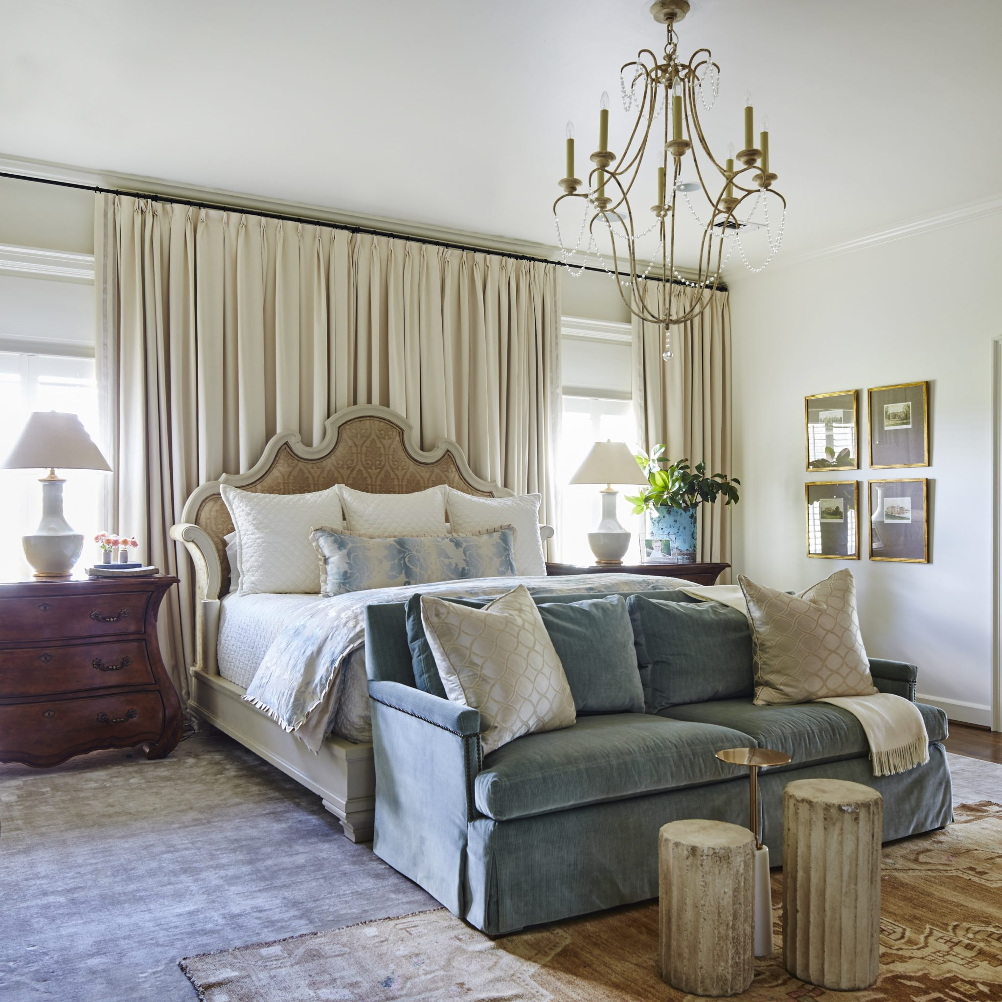 Cozy bedroom with velvet sofa, antique oushak rug and upholstered headboard. by Ashley Gilbreath Interior Design