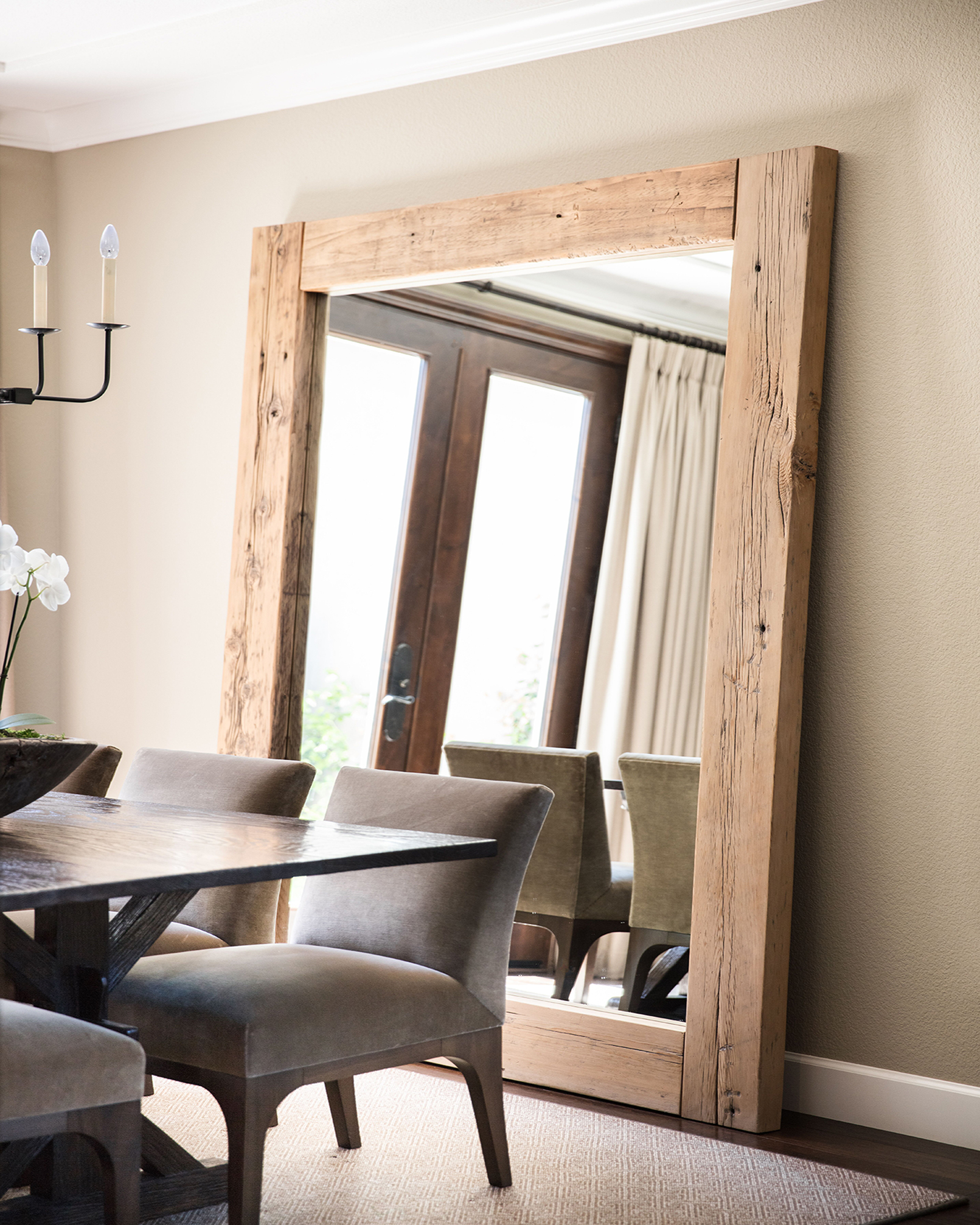 A striking mirror framed in reclaimed oak steals the show in the dining room. by Kriste Michelini Interiors