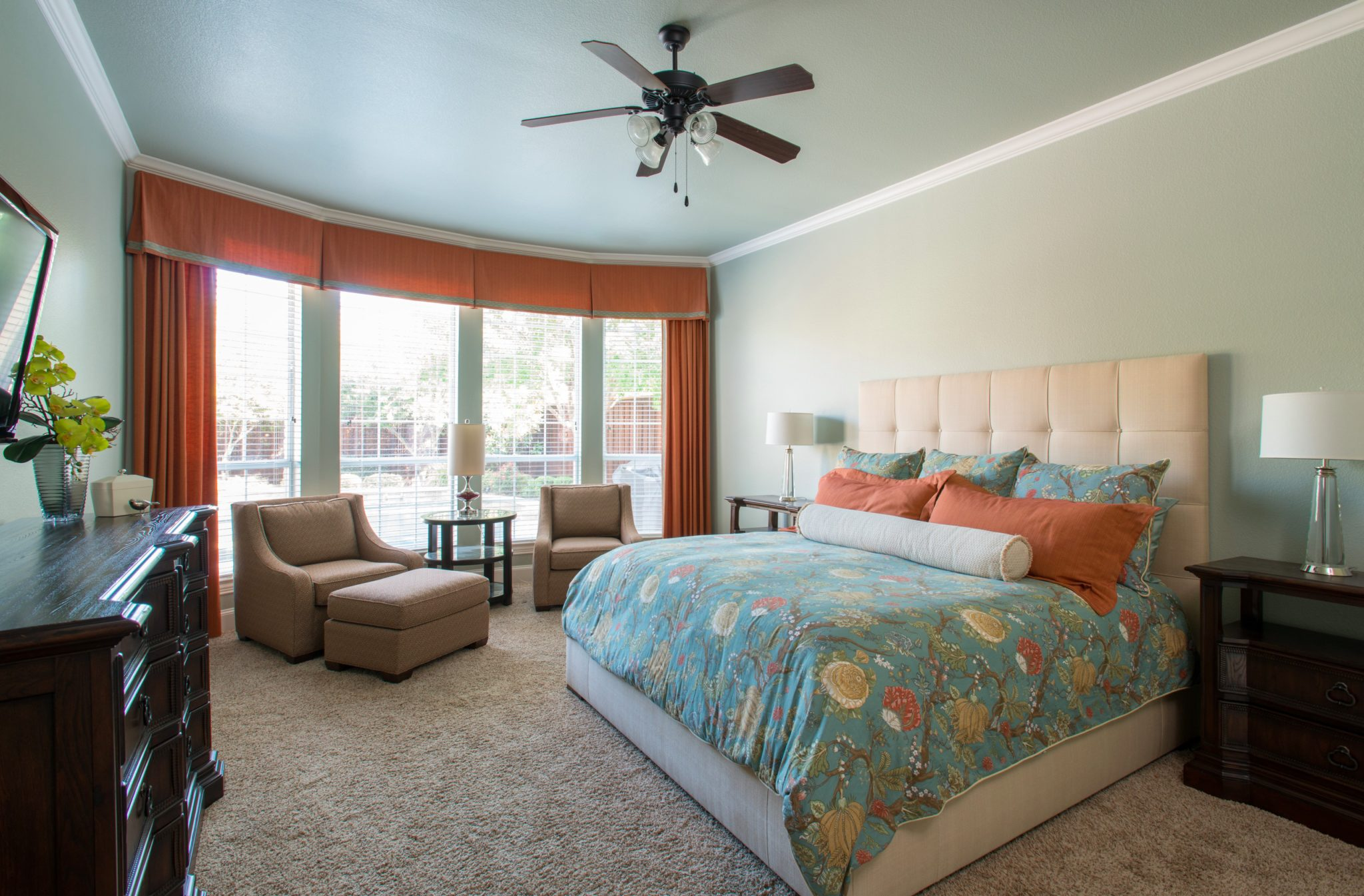 Transitional master retreat with pumpkin and steel blue by Nicole Arnold Interiors