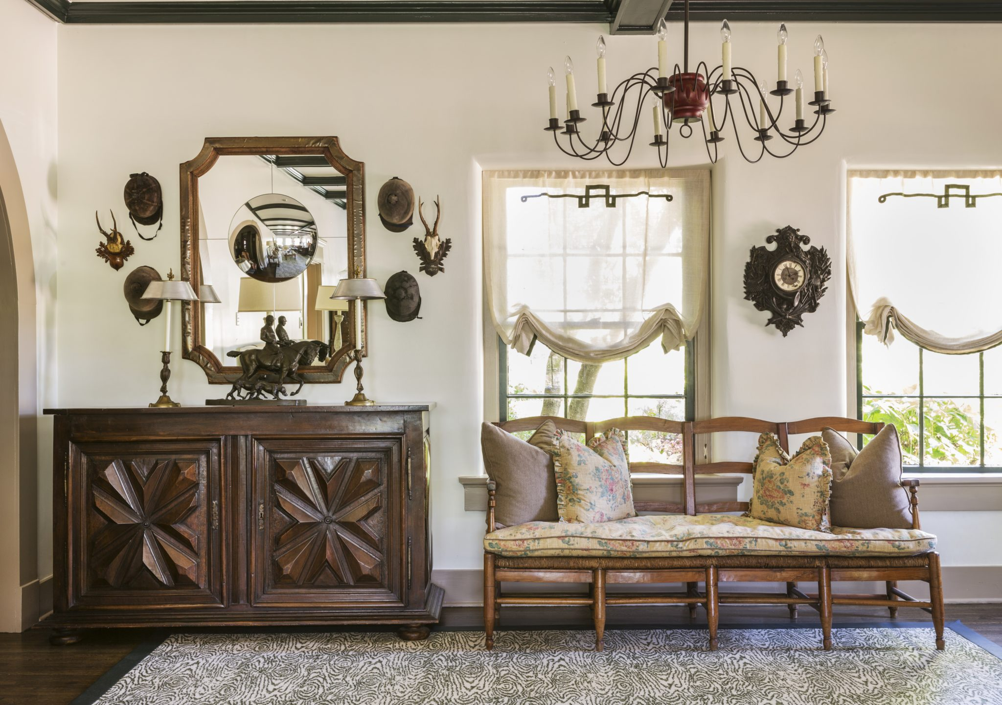 Foyer featuring collection of riding hats and mounts with an antique bench by Goddard Design Group
