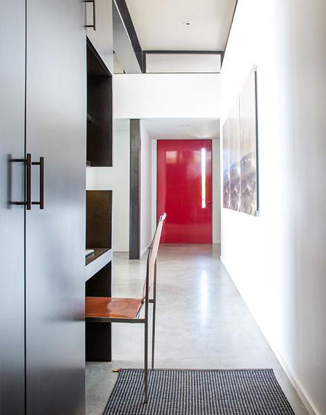 Black Residence - Concrete floor, Zele Company chair, and red steel front door by Elizabeth Vallino Interiors