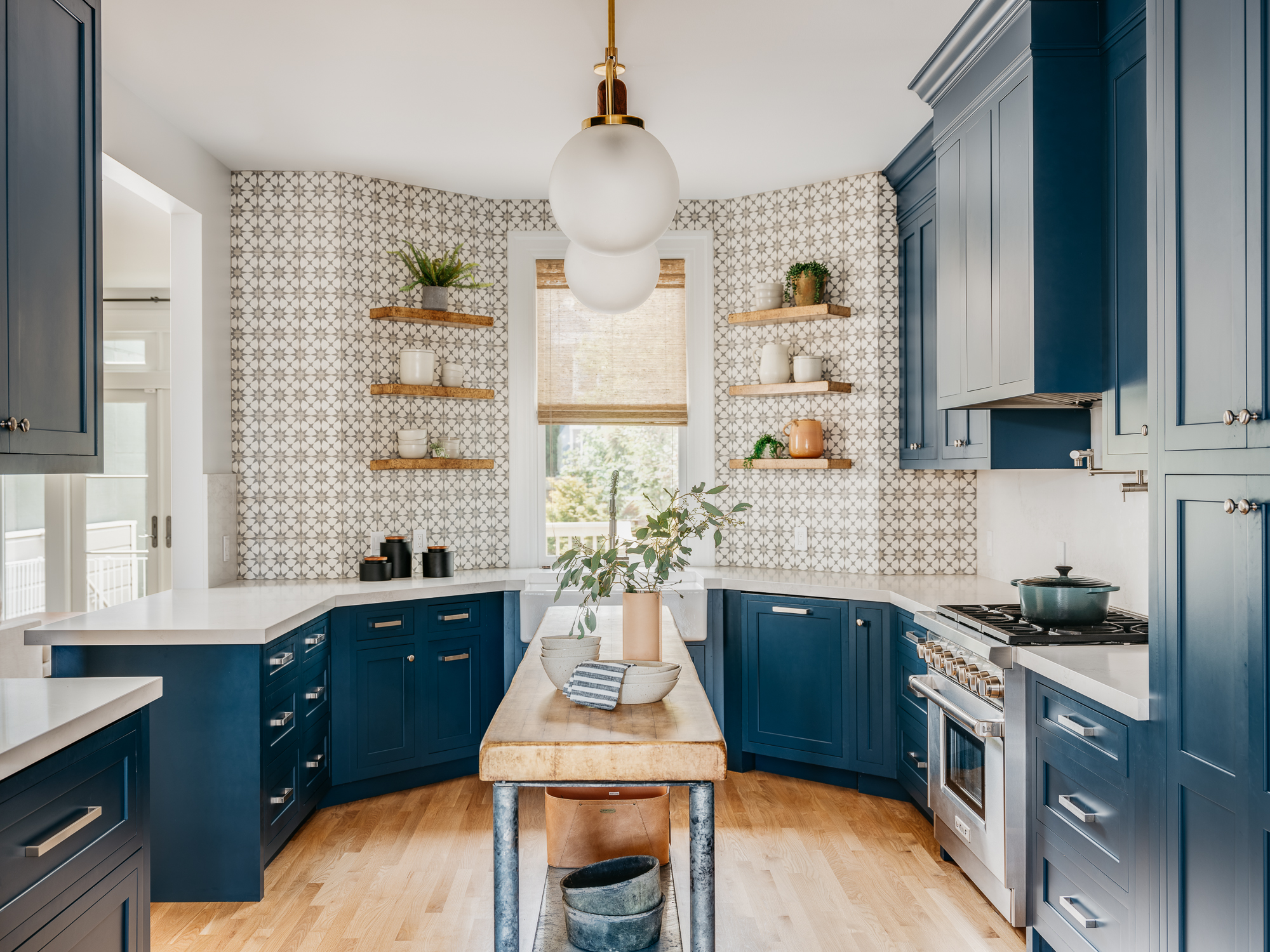 Blue and white kitchen with blue cabinets, patterned concrete tile backsplash. by IDF Studio