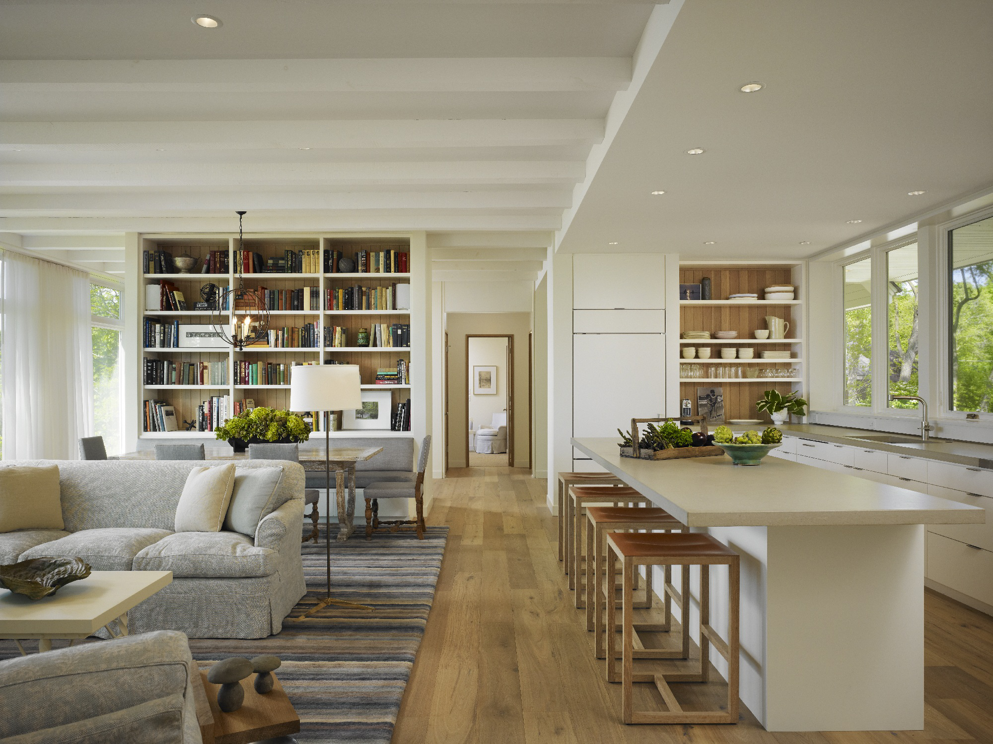 Painted beams, light oak floors and a concrete counter brighten this great room. By Robbins Architecture