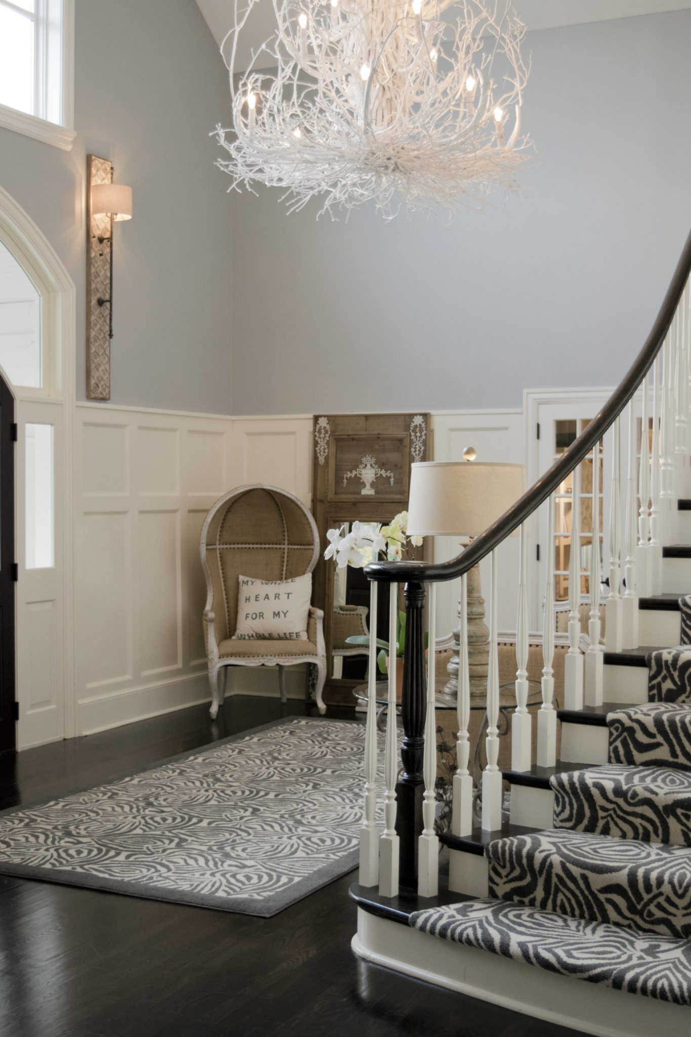 Gray and white foyer with curved staircase by LSM Interior Design