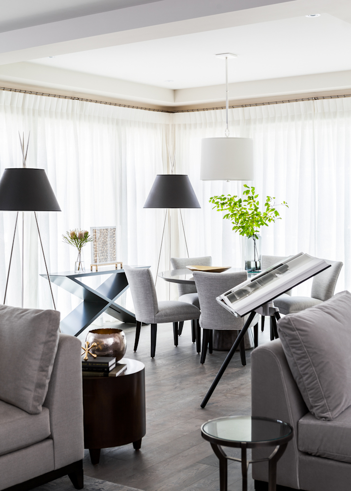 In the breakfast area, sunlight is softly filtered by sheer linen drapery from Kravet. Powell and Bonnell's large scale floor lamps and console add drama to this family space.