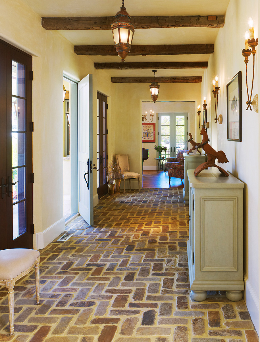This rustic foyer floor was laid with custom, tumbled-stone cobbles. By Barnes Vanze Architects, Inc.