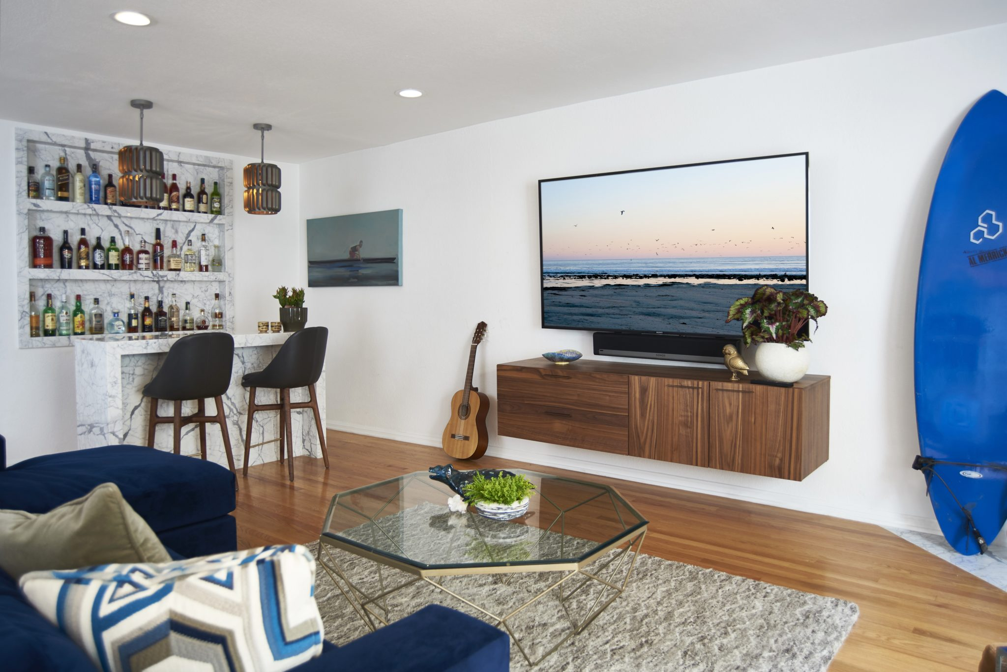 A custom Calcutta marble bar expands the living room's entertaining space. by Sarah Barnard Design