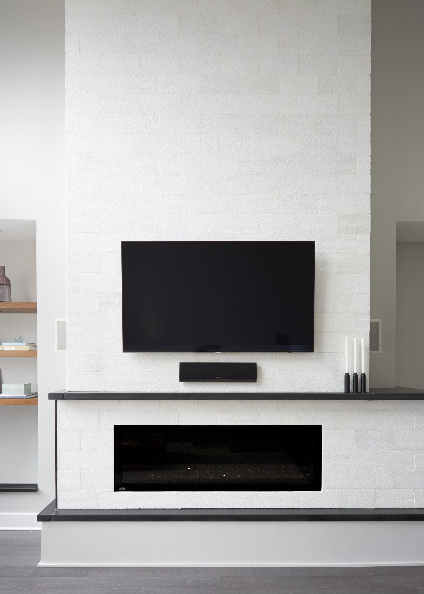 Modern condo with gas fireplace in living room, floating shelves, and concrete by Maren Baker Design