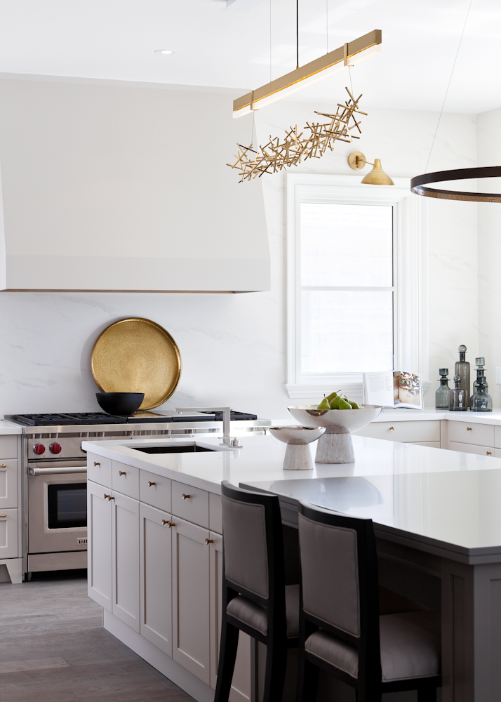The kitchen has a sleek, minimalist look with a bespoke ceiling light fixture by Ridgely Studio Works and a large-scaled hood and range that echo the fireplace design in the great room.