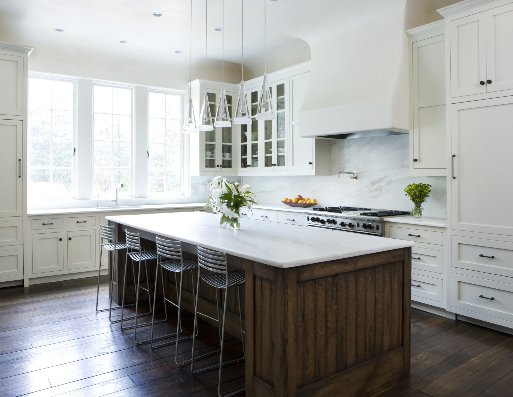 Large kitchen with wood floors and large island by James Michael Howard