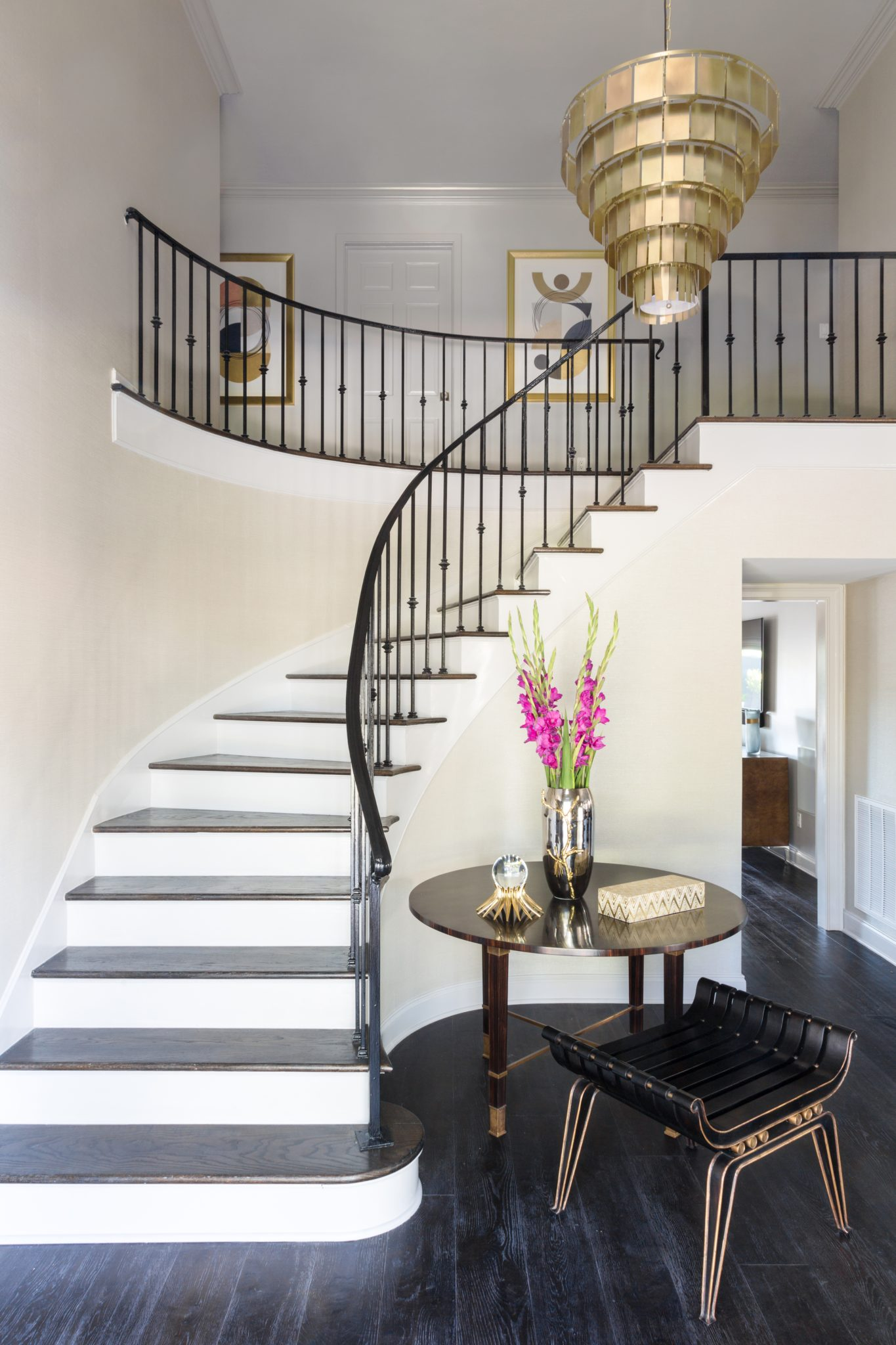 Foyer with metal tiered chandelier and custom entry table/seating by Eclectic Home