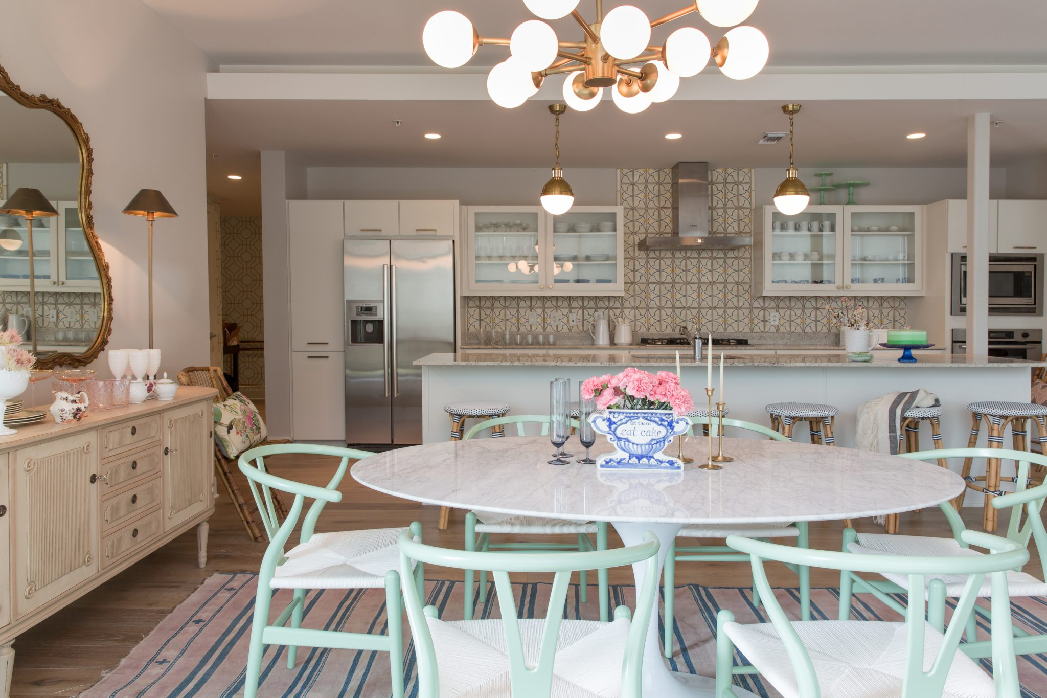 La Patisserie kitchen with wishbone chairs, gold globe lighting, and tulip table. By Maureen Stevens Design