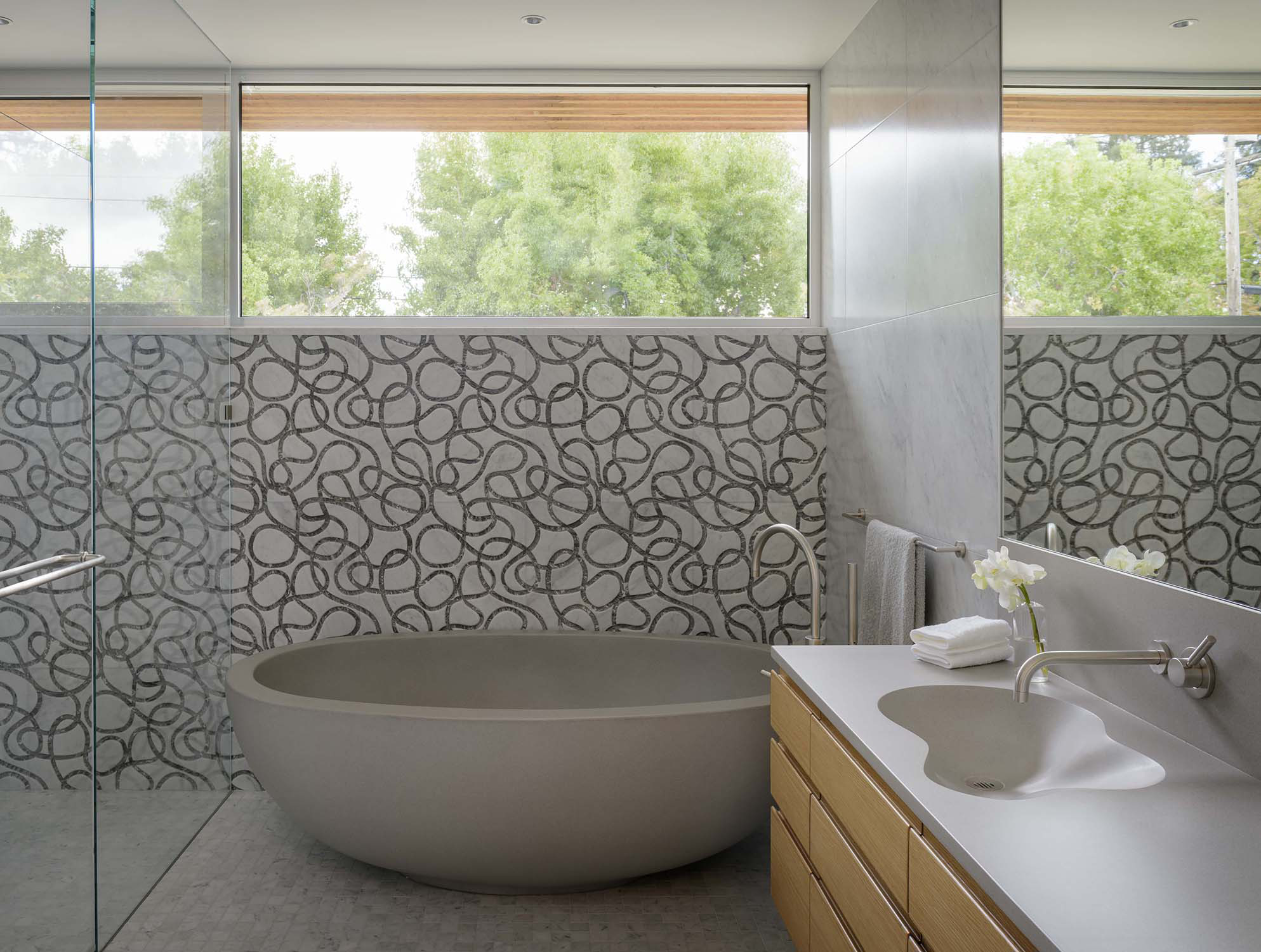 Freestanding concrete tub with carved marble wall tile by Verner Architects