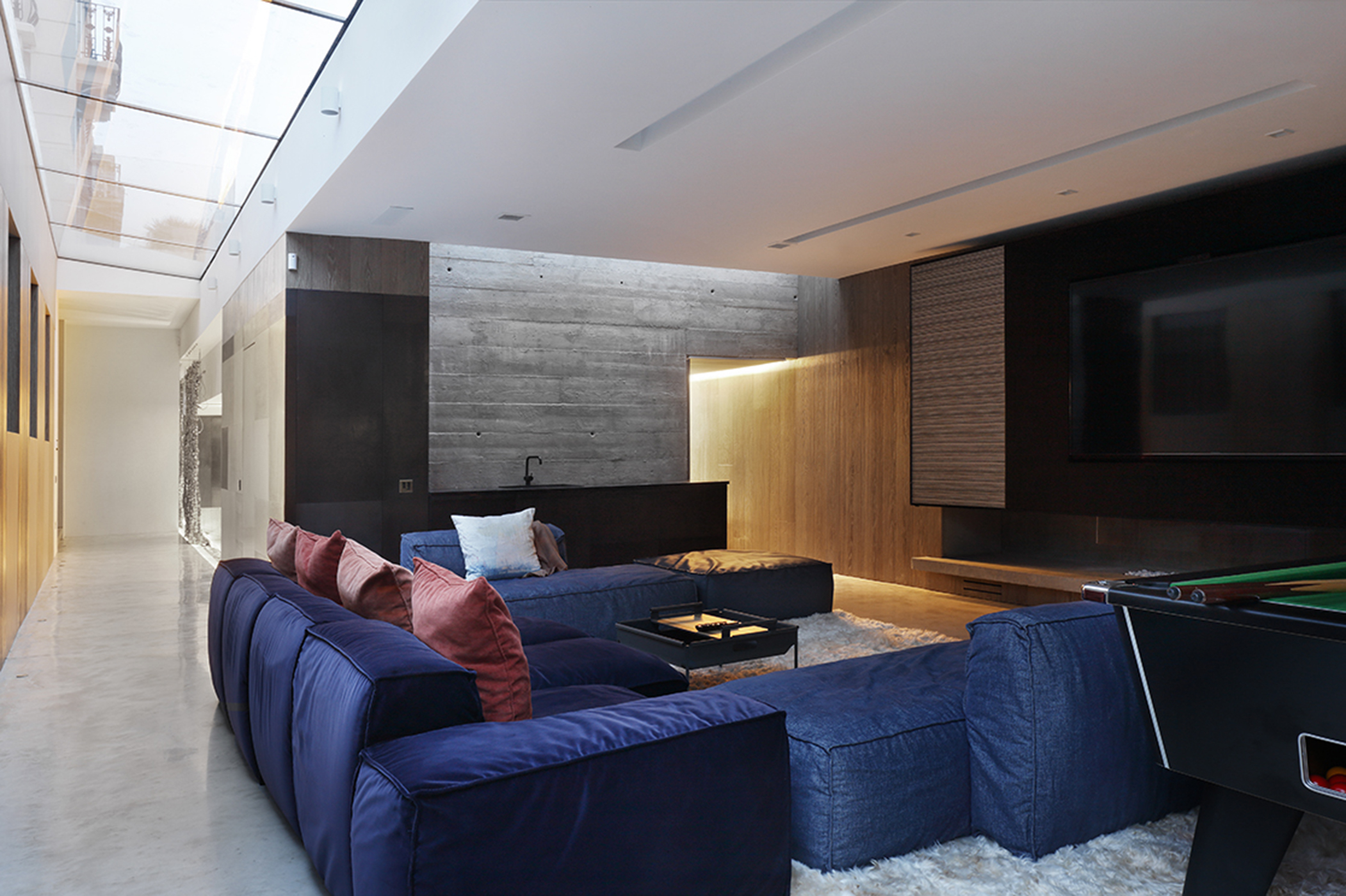 Cinema room mixes raw, cast concrete walls and warm wooden paneling. By Carden Cunietti