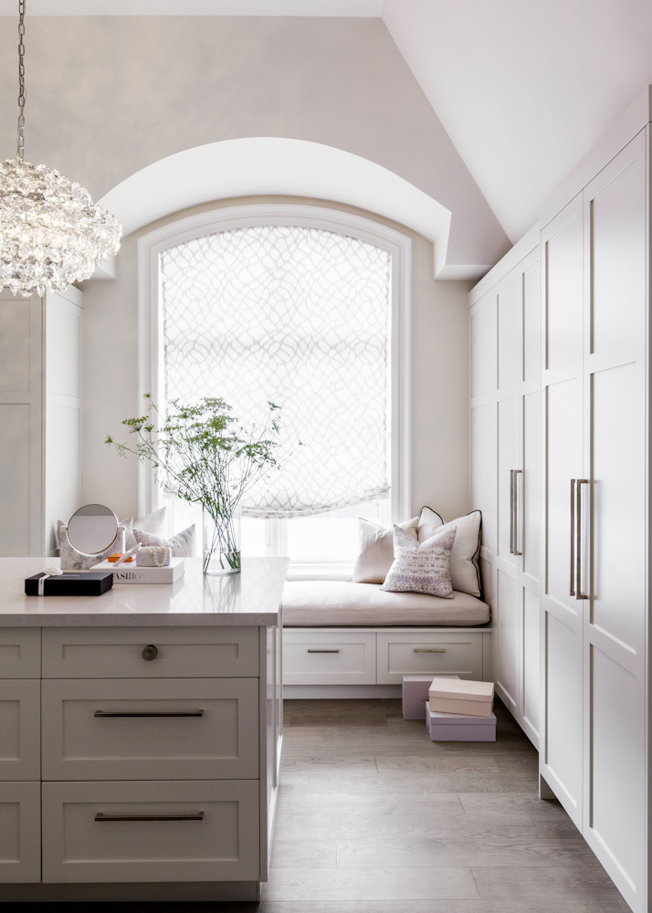 The walk-in closet is outfitted with custom cabinetry and a custom-made roman blind in a linen sheer fabric from Kravet. Brass hardware from Rocky Mountain Hardware and a crystal chandelier from Visual Comfort add a hint of glamour to the soft colors of the space.